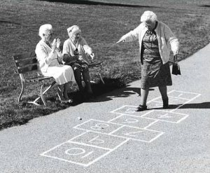 Image of an elderly lady playing hopscotch