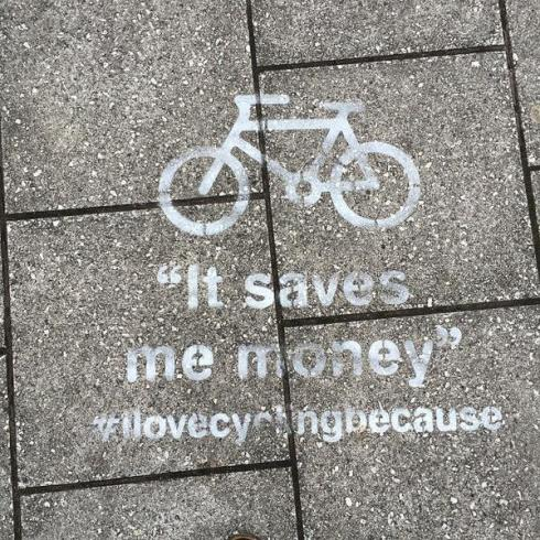 """Stencil on pavement saying """"I love cycling because it saves me money"""""""